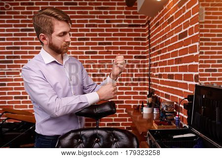 PPortrait of the hairdresser. Cheerful young bearded man fastens the buttons on the sleeve on his shirt. Armchair and instruments for barbershop. Professional and craftmanship. Hairdresser in the brown jacket. Background of brick wall.