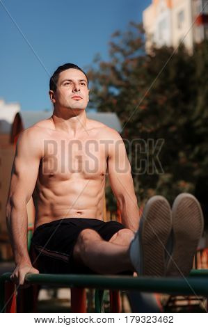 Young muscular build man doing pull ups exercises on horizontal bar outdoors, strong athletic man with naked torso training hard at sunny afternoon outside, sportsman working out. Healthy lifestyle.