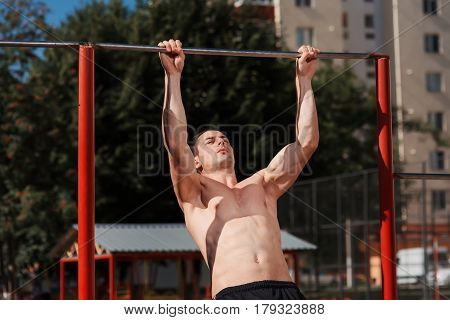Young strong athlete doing pull up exercise outdoors at street gym. male working out on horizontal bar in sunny day, sportsman do physical exercises. Abs. Healthy lifestyle.