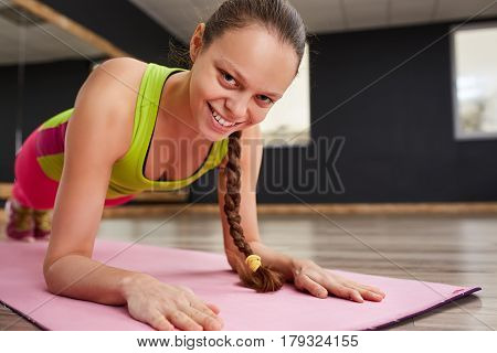 Portrait of a smiling young sporty woman stretching hands on pink exercise mat. Sporty woman in sport clothes, pink leggings and green t-shirt. In gym. Healthy lifestyle.