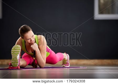 Woman practicing yoga in the splits position on the floor. In the gym. Sporty woman in the sporty clothes, pink leggings and green t-shirt. Healthy lifestyle. Portrait of the yoga woman on the mat.