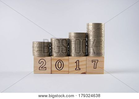 Close up of wooden blocks number 2017 with stacked silver coins on wooden block isolated on white background. Business and Financial concept.