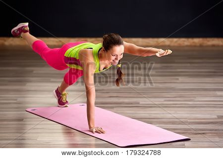 Slim fitness young woman Athlete girl doing exercise with legs on the pink yoga mat. concept training workout crossfit gymnastics cross fit. Healthy lifestyle. Woman in the sporty clothes.