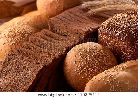 Assortement of Freshly baked traditional bread with ears of wheat. Sliceas of the bread and rulls. Background of bread. Delicious food. Fresh baking. Tasty and appetizing.