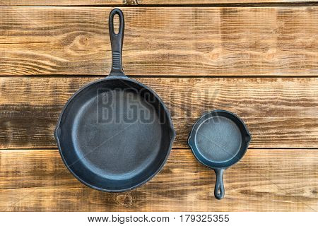 Cast-iron Frying Pans on Rustic Wooden Background