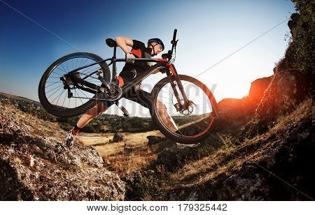 Professional Cyclist Taking his Bike up the Rocky Trail at evening. Extreme Sport Concept. Background with beautiful landscape, sunset, sunrise. Low angle and fisheye. Sportsman in the sportwear, helmet and sunglasses. Travel in the countryside.