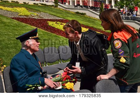PYATIGORSK RUSSIA - MAY 09 2011: Volunteers offers help to a veteran on Victory Day. The end of the Second World War