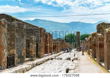 POMPEII, ITALY - MAY 13, 2014: Tourists visit the ruins. Pompeii is an ancient Roman city died from the eruption of Mount Vesuvius in 79 AD.