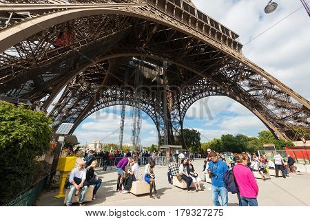 PARIS - SEPTEMBER 20, 2013: Tourists visiting the Eiffel tower. The Eiffel tower is one of the major tourist attractions of France.
