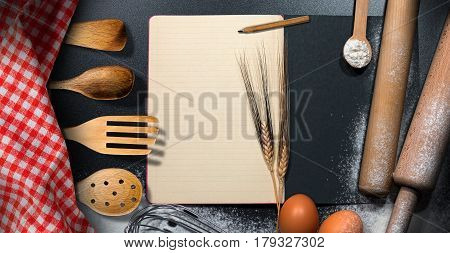 Empty recipe book with lined paper on a baking background with flour ears of wheat eggs kitchen utensils and a checkered tablecloth