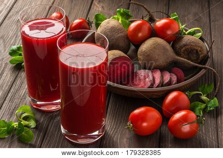 Healthy eating dieting and vegetarian concept - glass juges of beet-tomato juice with vegetables on dark wooden background . Detox and healthy diet .