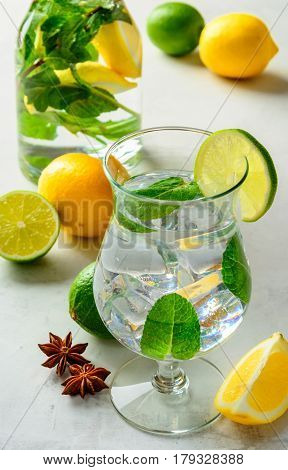 Homemade refreshing summer lemonade in a glass with lime lemon and mint on a white concrete or stone background.
