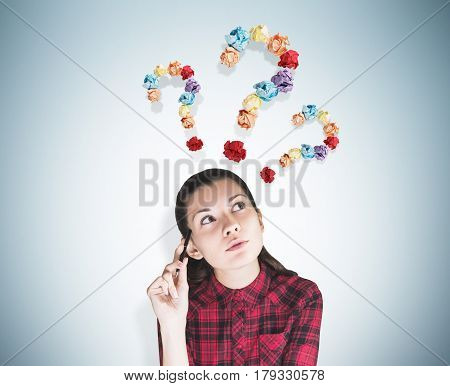 Portrait of a geeky young woman wearing a red checkered shirt and sitting with a pen near a gray wall. There are three question marks made of colorful paper balls above her head.