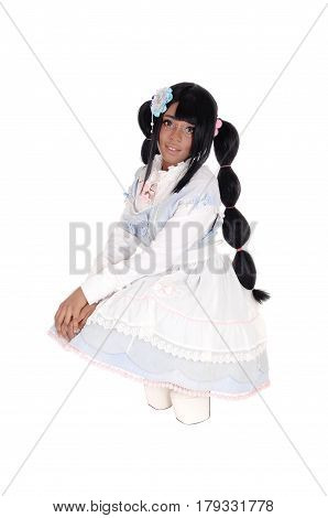 A lovely African American woman crouching on the floor in a baby doll dress and long black hair isolated for white background.
