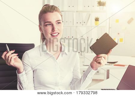 Portrait of a cheerful blond businesswoman holding a notebook and a pen and sitting in her office planning her workday. Sunlight. Toned image.