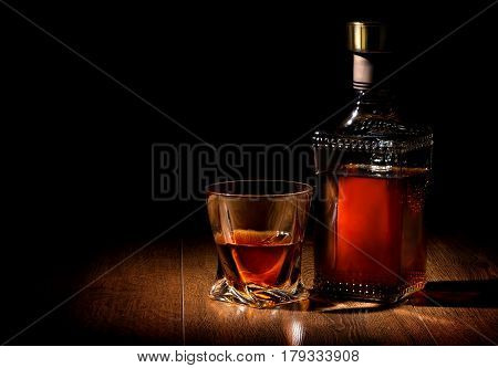 Bottle and glass of whiskey on a wooden table