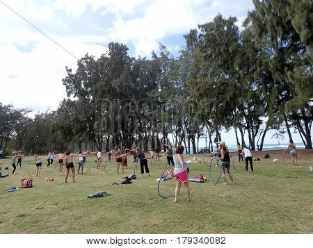 NORTH SHORE HAWAII - FEBRUARY 23: PPeople spin hula hoops during outdoor hooping class at Wanderlust yoga event on the North Shore Hawaii on February 23 2017.
