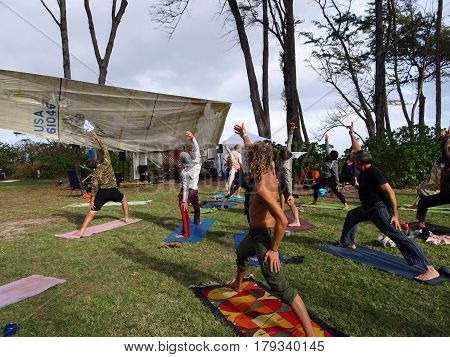 NORTH SHORE - FEBRUARY 19: Outdoor Yoga class led by Kara Miller does warrior z among large ironwood trees at Optimysstique Campout 2017. February 19 2017 Oahu Hawaii.