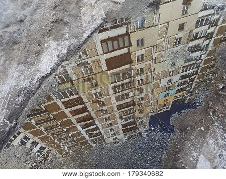 The Diagonal Reflection Of The Building Is Brown In A Puddle On The Asphalt, Along The Edge Of The P