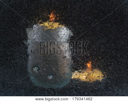 Two Candles, Shot Through A Glass With Air Bubbles: Vague Silhouettes Of Candles On A Black Backgrou