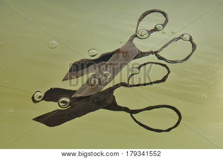 Old Vintage Metal Scissors In Water, Silhouettes Distorted By Water, Air Bubbles, Green Background.