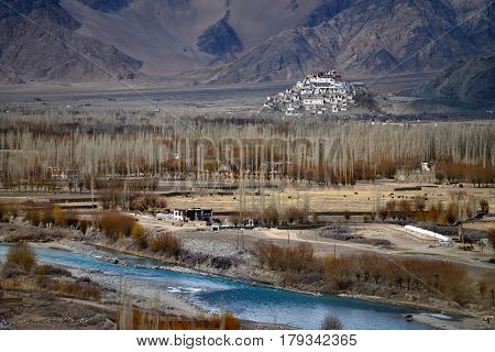 Buddhist Monastery Tiksey Gonpa In Ladakh: In The Foreground The River Bed Of The Indus With Bright