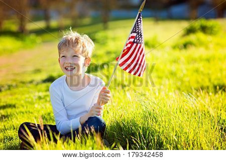 happy proud caucasian boy holding american flag celebrating 4th of july outdoors