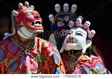 Buddhist mystery with the performance of Cham Dance in the Tibetan monastery in Zanskar: red white and blue masks with skulls bright red robes of monks black background Ladakh Himalayas India.