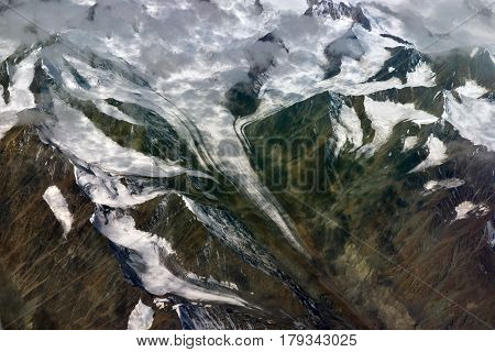 A Long White Glacier Slides Down From The High Mountains And Snow-capped Peaks Of Peaks, A Photograp