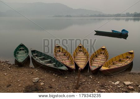 Green And Yellow Wooden Boats On The Shore Of Lake Feva, The Calm Water Of The Lake As A Mirror Refl