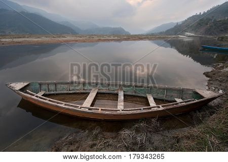 A Large Old Wooden Boat Across The Shore On Lake Feva, The Water Reflects A Gloomy Gray Sky, In The