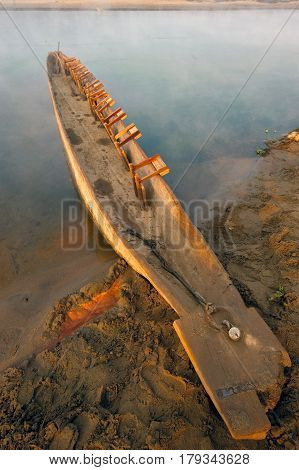 A homemade wooden fishing boat canoe on the river bank diagonally in the frame is colored by the light of the sunrise in orange on the blue background of the river Chitwan Nepal.