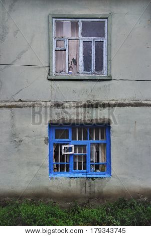 The wall is an old stucco house with two windows: a boxier gray window with a wooden frame and curtains the bottom window is a bright blue color and an open white section under the walls green grass.