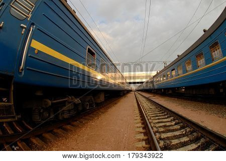 Two trains with blue wagons and between them rails all converge to one point on the horizon.