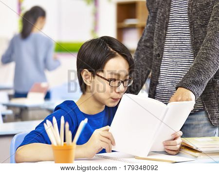 asian elementary schoolboy getting help from teacher or tutor in classroom at school.