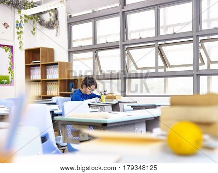 asian school boy studying alone in classroom.