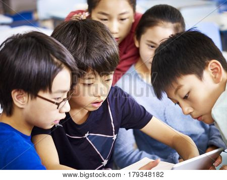 group of asian elementary schoolchildren playing game using tablet together.
