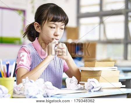 asian primary school schoolgirl crumbling a piece of paper out of frustration.