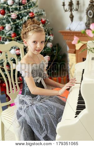Little girl 7 years, elegant Princess dress , is sitting at an old white grand piano.She plays music.