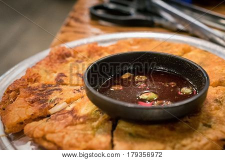 Korean pancakes with spicy dipping sauce with cutting utensils in background