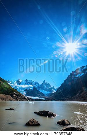 Long exposure of Laguna Torre in Patagonia in Argentina, with Cerro Torre in the background, and lens flares with direct shot into sun.