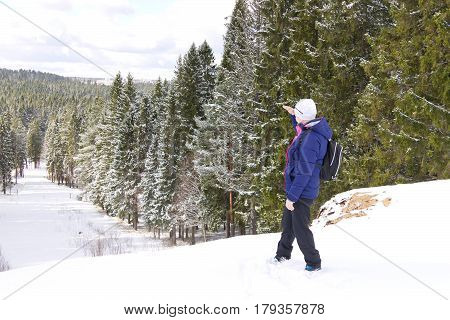 Middle-aged female traveler standing on top of a hill against the winter forest background also looking afar. Northern Russia in winter