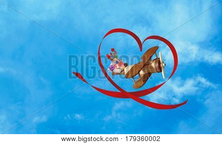 Toy wooden plane flies to congratulate on the holiday favorite in blue clouds sky