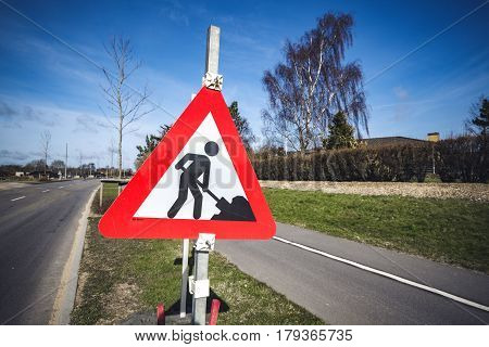 Road construction sign by a roadside in a city on a sunny day with blue sky