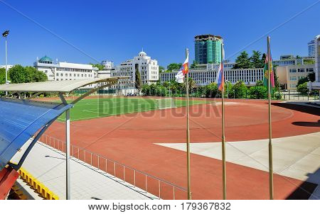 A well-equipped stadium for various sports and competitions with a big football field running track bleachers for spectators. The City Of Sochi Russia.