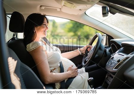 Pregnant woman driving with safety belt on in the car