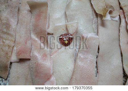 little red shine heart lay on fresh pig pink skin