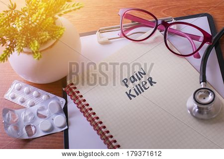 Stethoscope On Note Book With Pain Killer Words As Medical Concept.