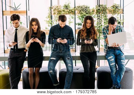 Group Of Friends Standing On Table And Browsing In Their Divices In Modern Room