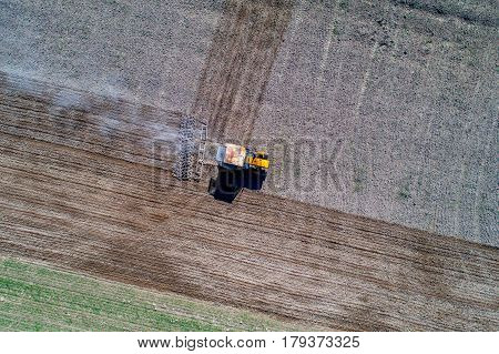 Aerial view on the tractor harrowing the field